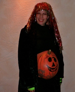 I wish I had a pic of her in her sassy Spider Woman dress.  Alas, I don't.  But this was her clever concoction the year she was pregnant with her daughter.  The pumpkin IS her belly--painted.